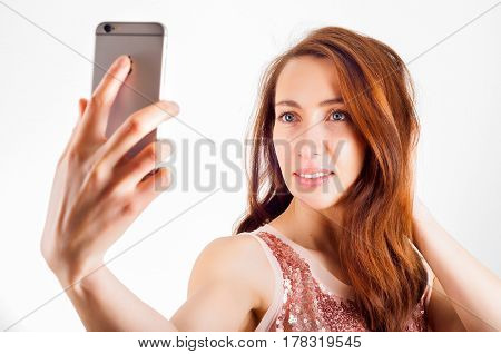 Young woman using her smart phone to shoot a selfie and smiling.