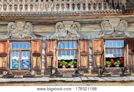 Windows of old traditional Russian log house with carved wooden trim and red geranium flowers