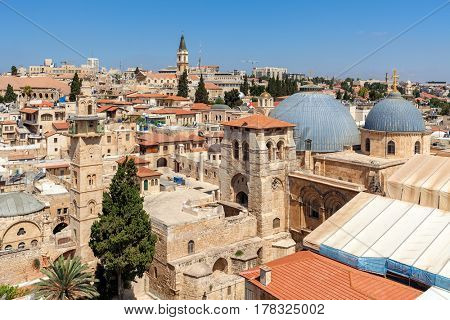 Church of the Holy Sepulchre domes, minarets and rooftops of the Old City of Jerusalem, Israel as seen from above.