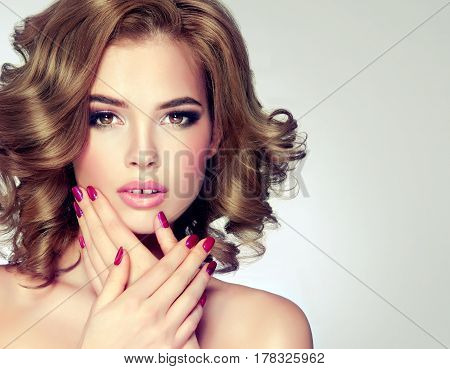 Girl with  shiny wavy medium length hair . Beautiful model with curly hairstyle . Purple manicure on nails