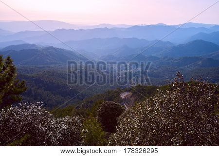 Small mountain village among ridges in the blue haze near the Troodos mountain range in a beautiful sunny evening. Troodos Cyprus.