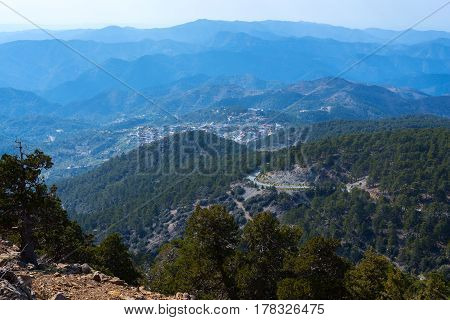 Magical view of small mountain village among ridges in the blue haze near the Troodos mountain range in a beautiful sunny evening. Troodos Cyprus.