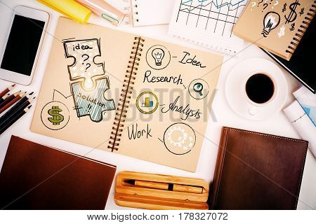Top view of white office desktop with creative sketch in spiral notepad coffee cup blank smartphone supplies and other items. Analysis concept