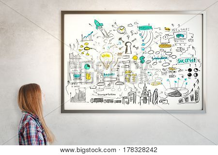 Side portrait of girl looking at frame with colorful business sketch. Concrete wall background. Communication concept