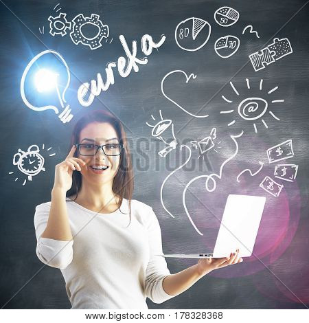 Attractive young woman with laptop in hands on concrete background with eureka exclamation and drawings. Creative idea concept