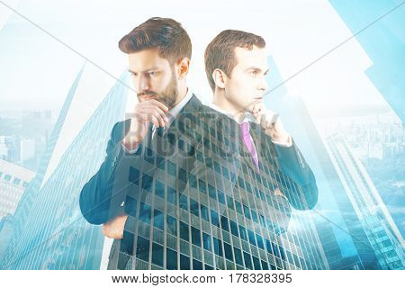 Two handsome thoughtful men on blue city background. Teamwork concept. Double exposure