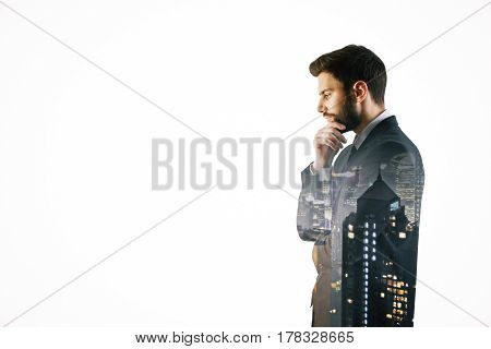 Side view of thoughtful young businessman on night city background and copy space. Future concept. Double exposure