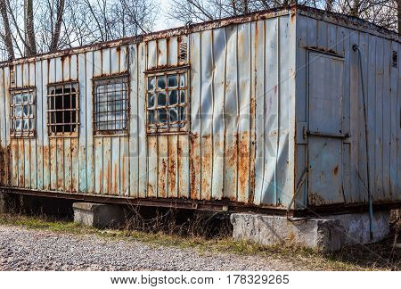 Old rusty metal trailer with grates on the windows.