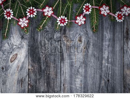 Festive garland of fir branches and decorative felt snowflakes on a gray wooden surface empty space