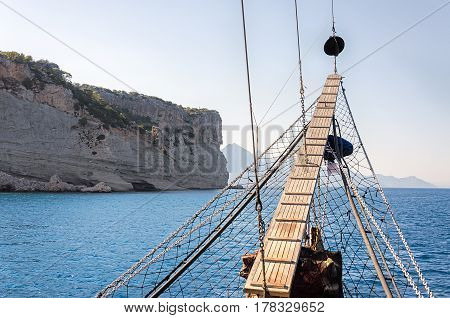 Wooden bowsprit of an old sailing ship against the backdrop of the mountains Turkey.