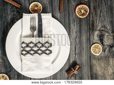 White dish with cutlery knife with fork wrapped in a napkin top view