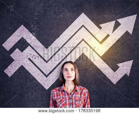 Pretty girl with drawn chart arrows on concrete background. Success concept