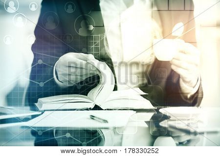Close up of young woman's hands holding coffee cup and flipping pages with digital chart pattern. Accounting concept
