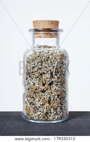Dried wormwood herb inside a glass jar. Herbs and plants for tea.