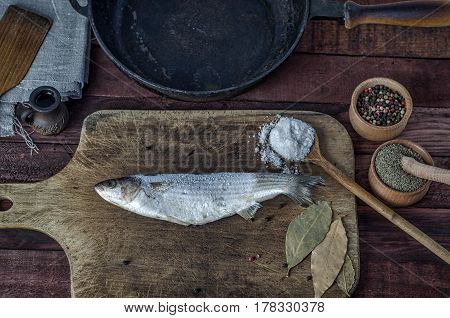 Frozen fish smelt on a kitchen cutting board near a spice and frying pan