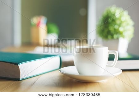 Close up of wooden desktop with ceramic coffee cup green hardcover book blurry plant and supplies. Workplace concept