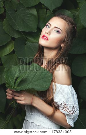 Portrait of a young woman in nature in her hands she is holding a green leaf of a tree.
