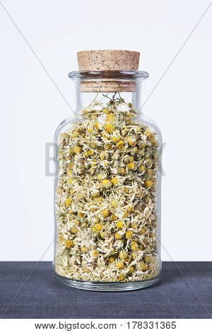 Dried chamomile herb inside a glass jar. Herbs and plants for tea.
