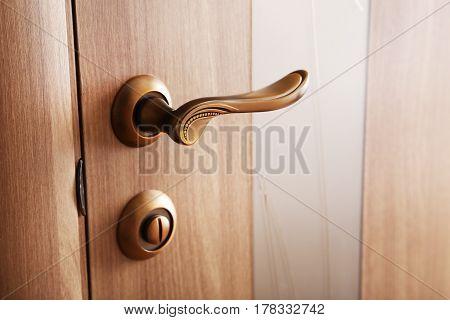 Brown door handle on the wooden door
