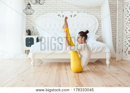 Woman gymnast carries out exercise it in his bedroom.