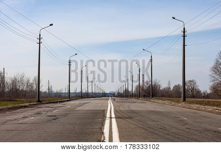 The asphalt road with double solid white center-lines and rows of lanterns along the both sides. Outskirts of Kyiv. Early spring.