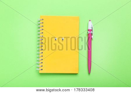 Notebook and pen with googly eyes on a green background