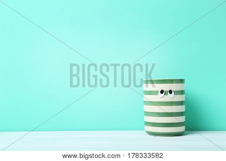 Striped Cup With Googly Eyes On A Green Background