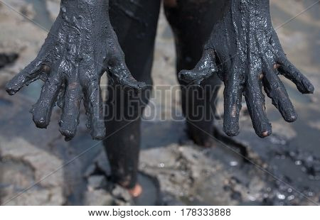Woman's hands smeared with black healing mud.