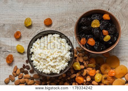 Cottage Cheese In White Plate And The Prunes In The Brown Plate. Prunes, Dried Apricots, Dried Manda