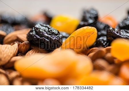 Prunes, Dried Apricots, Dried Mandarins And Almonds On A Light Wooden Background