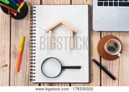 Search For House or Flat Real Estate Concept On Work Desk With Notebook And Magnifying Glass