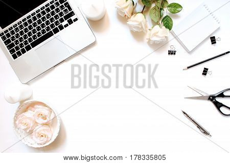 Minimalistic feminine workplace with laptop keyboard, pen, white candles, office clips and roses in flat lay style. White background, top view, frame poster