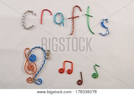 Jewelry wire bent into the shapes of bass clef treble clef and music notes along with the letters to spell the word