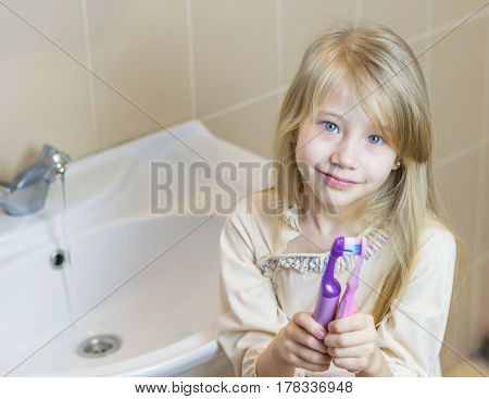 Two different toothbrushes kiss the girl in his hands. The concept of oral care.