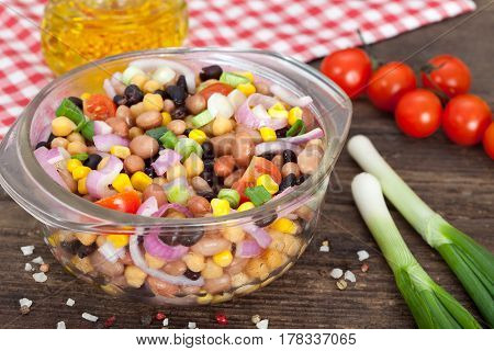 Three bean salad with sweetcorn, chickpeas and red onion in a vinaigrette dressing.