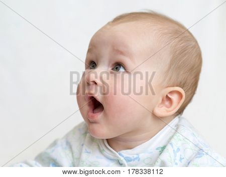 Boy smiling open mouth with no teeth on a light background