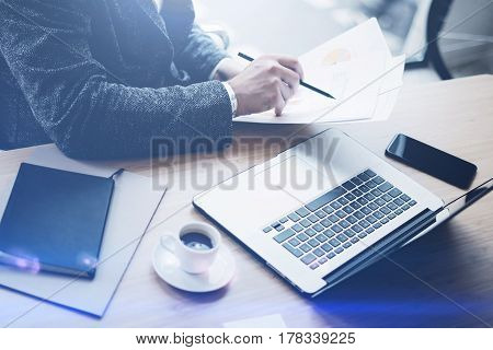 Adult businessman working at sunny office on laptop while sitting at the wooden table.Man analyze document in his hands.Blurred background.Visual effects