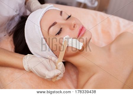 The doctor is a cosmetologist for the procedure of cleansing and moisturizing the skin applying a mask with stick to the face of a young woman in beauty salon.Cosmetology and professional skin care.