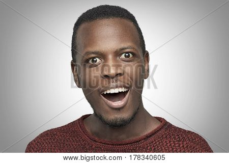 Close-up portrait of African American man wearing casual red sweater having amazed and surprised look opening mouth widely. Headshot of surprised joyful black student shocked with unexpected success