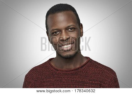 Handsome young African American male dressed in casual sweater looking at camera with happy smile. Close up portrait of dark-skinned student smiling with his white teeth isolated on grey background