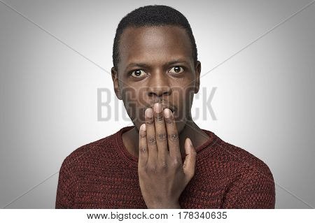 Astonished bug-eyed dark-skinned student wearing casual red sweater covering his mouth with one hand looking shocked. Surprised embarrassed and confused African Ameican male showing omg emotion.