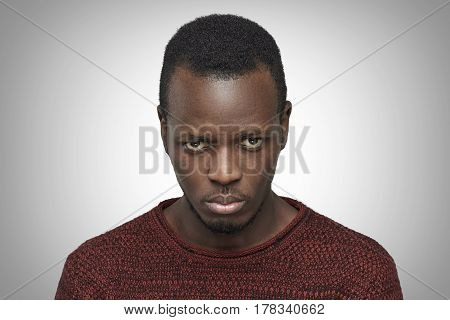 Close up portrait of displeased upset and pissed off young African American male. Black man looking and frowning at camera having bad mood feeling dissatisfied. Negative human face expressions