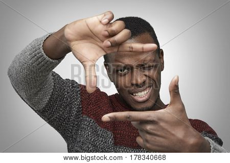 Close up portrait of young African American male in warm casual sweater making frame with his hands looking at camera and smiling standing against isolated grey background. Dark-skinned photographer
