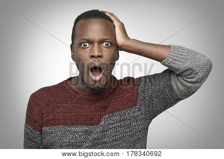 Portrain of terrified young African American man in casual sweater. holding hand on his head and screaming with horrified look opening mouth widely. Black male feeling scared or stressed. OMG concept