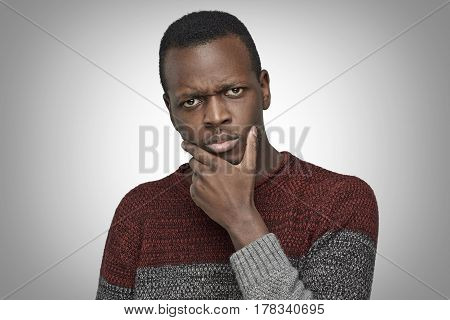 Close up portrait of serious puzzled African American male touching his chin looking thoughtful and skeptical about something. Dark-skinned student deep in thoughts hesitating to make decision