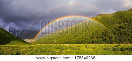 On the lawn among high green mountains stands a tourist tent and above it appeared a bright colorful rainbo on a summer day. Upper Svaneti Georgia Europe. Happy lifestyle. Beautiful universe.