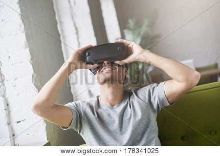 Handsome guy wearing gray t-shirt play with virtual reality glasses sitting on couch at home. Mobile gaming applications at home. Using mobile apps with innovative 3d goggles. Using VR technology