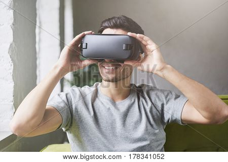 Close up of caucasian male wearing grey t-shirt and goggles experiencing virtual reality. European man playing video games using oculus sitting on sofa at home. VR technology gaming concept