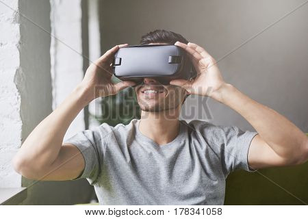Technology science innovation and cyberspace concept. Portrait of young attractive caucasian male wearing vr goggles. White man experiencing virtual reality using 3d in modern coworking studio