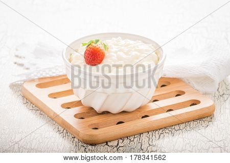 Bowl of creamy rice pudding garnished with a ripe whole strawberry.